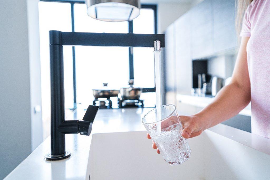 Osoba nalewająca wodę z kranu do szklanki
